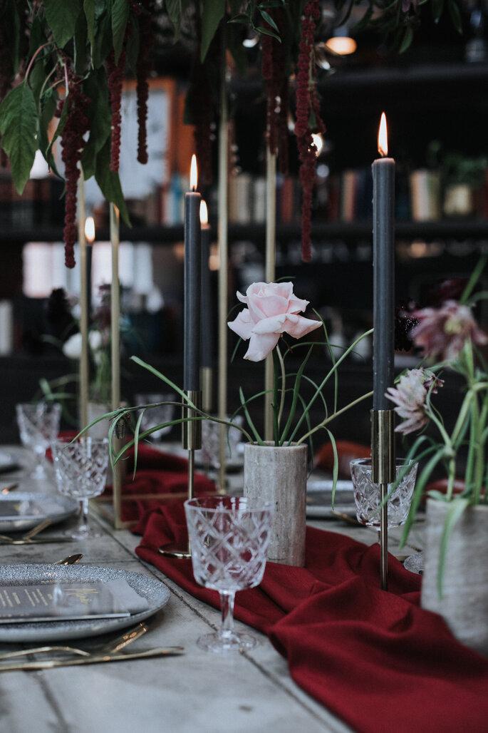 Hochzeitstisch dekoriert mit Blumen, goldenen Ständern und schwarzen Kerzen von Kopflegenden, organisiert von Freakin' Fine Weddings.