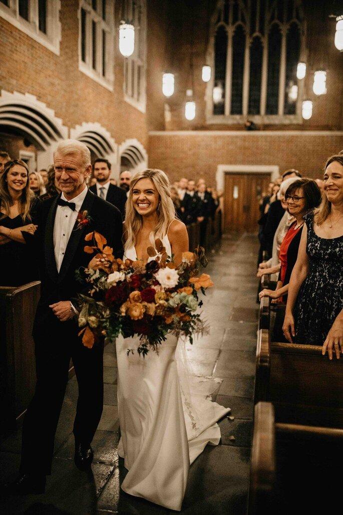 Lachende Braut mit Brautvater in Kirche