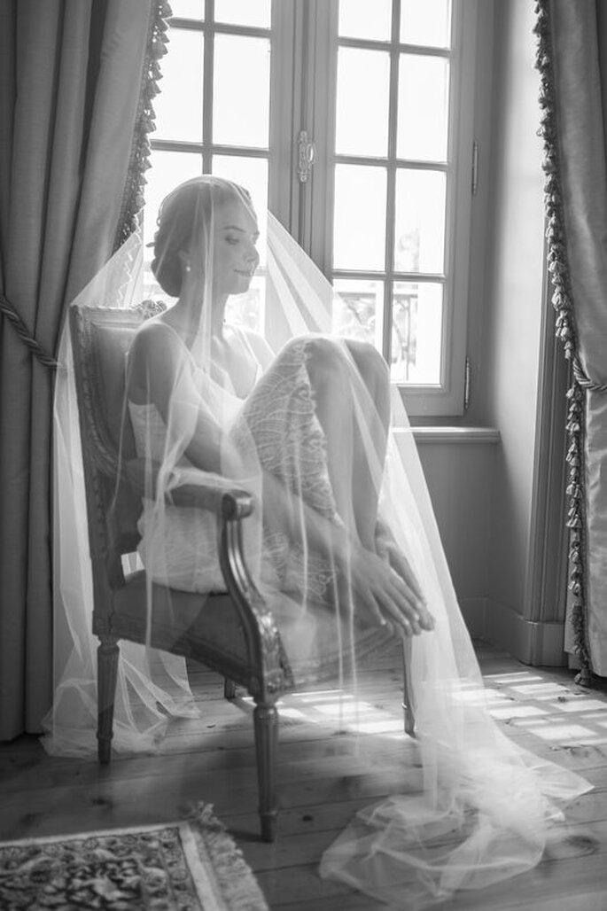 Alexandre Moulard : une mariée assise sur une chaise vintage pose derrière son voile qui la recouvre entièrement, pour un cliché artistique