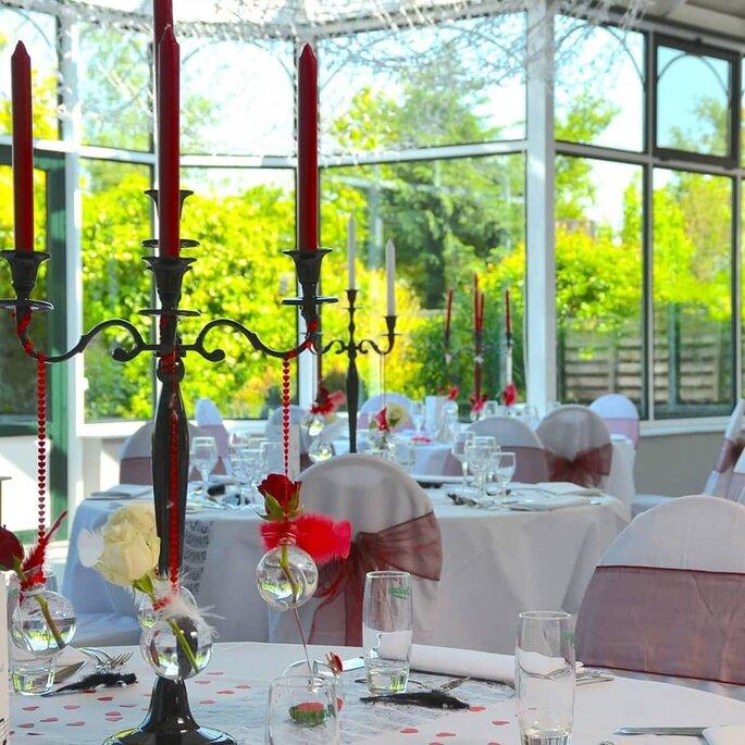 Bougeoirs ornés de pampilles et de fleurs dans des bulles d'eau en guise de centres de tables