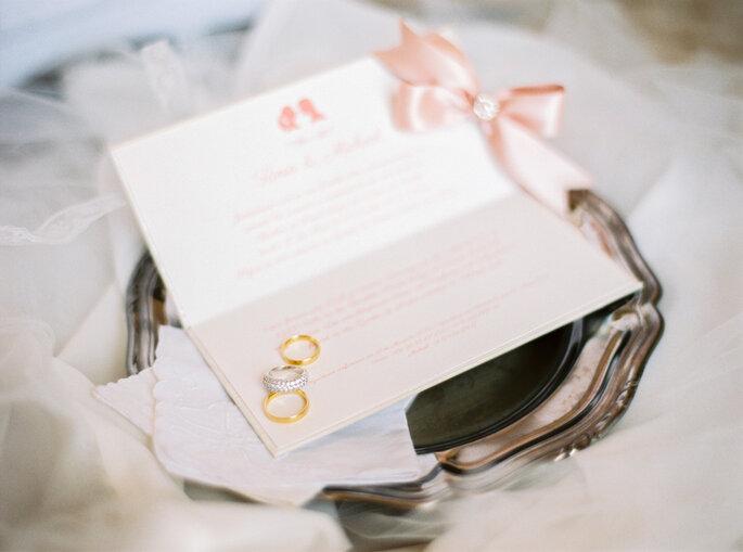 alianças de casamento em cima de um convite numa bandeja