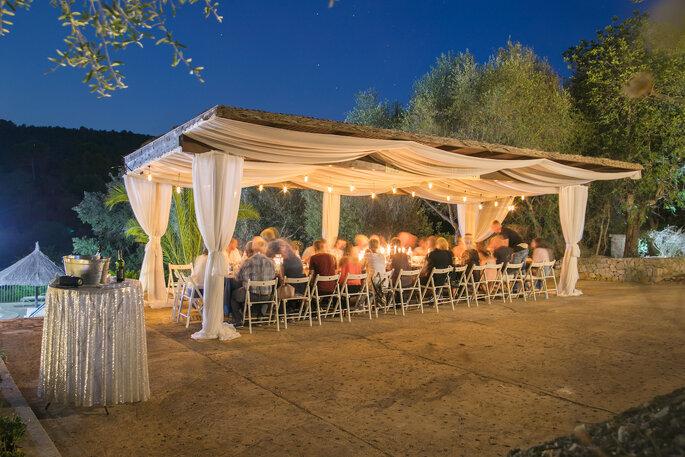 Eine Hochzeitsgesellschaft feiert in einem Zelt im Freien.