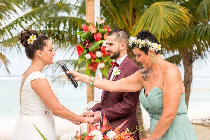 Une officiante de cérémonie laïque participe à l'échange de vœux de mariés, sur une plage - décor tropical