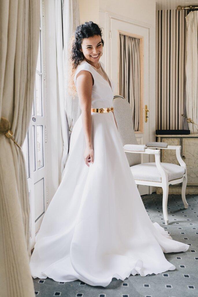 Une mariée avec un grand sourire, posant dans sa robe blanche