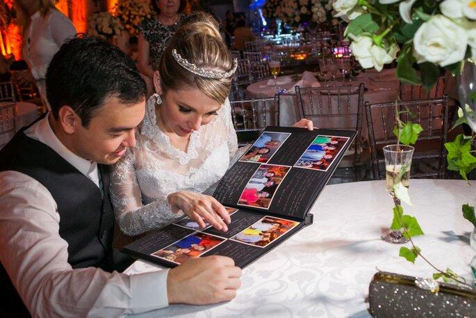 Noivos vendo livro de assinaturas com fotos no casamento.