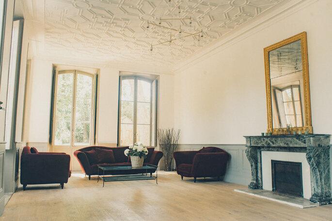 Un salon lumineux, de grandes baies vitrées, décoration sobre et chic, fauteuils bordeaux