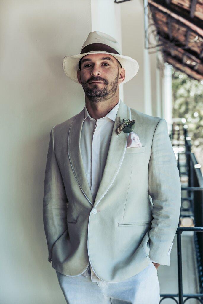 Novio con traje en lino color crudo y sombrero tipo panameño