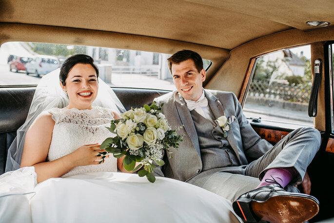 Das Brautpaar im Hochzeitsauto, Foto von Hüttner Fotografie.