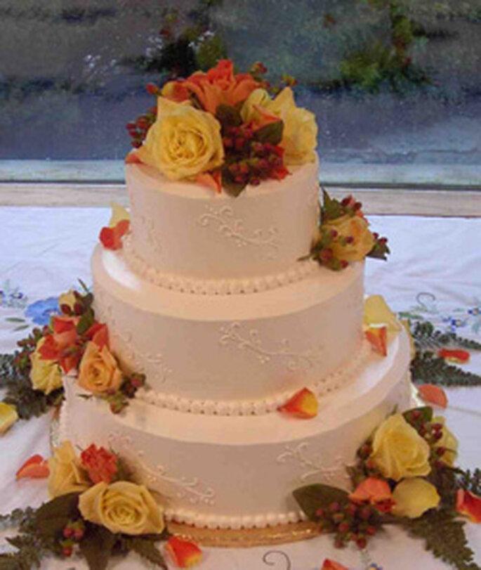 Una torta bianca, abbellita da fiori colorati