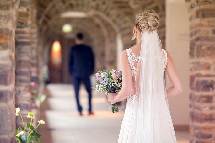 Ein Brautpaar von hinten fotografiert.