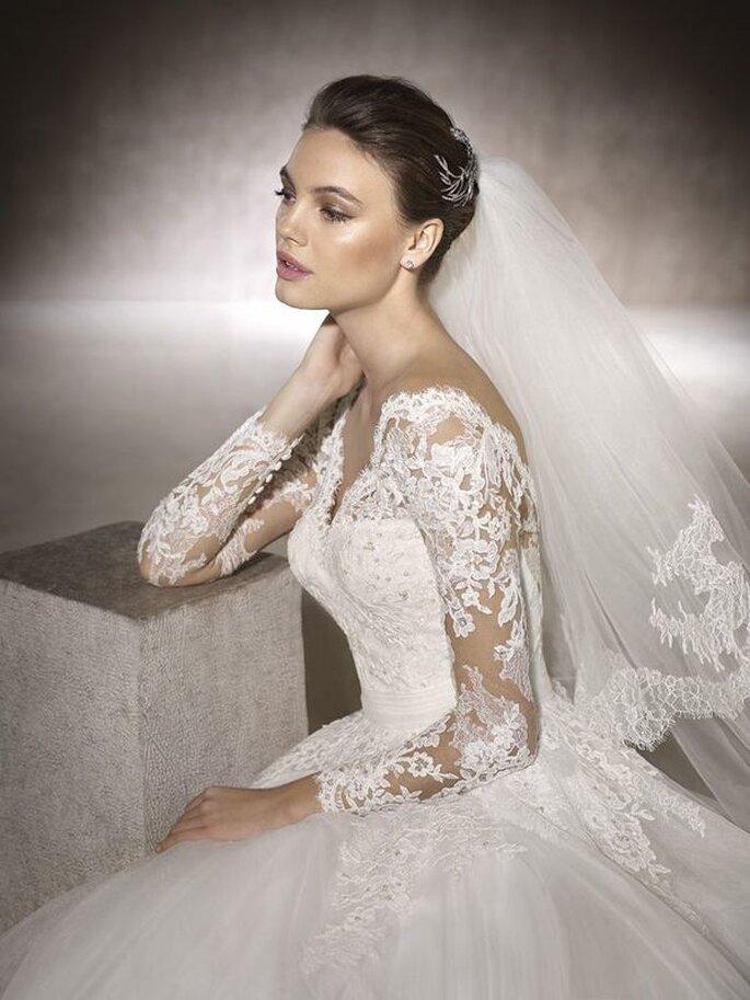 Une mariée portant une robe revêtant de la dentelle le long des manches et et descendant dans le dos.