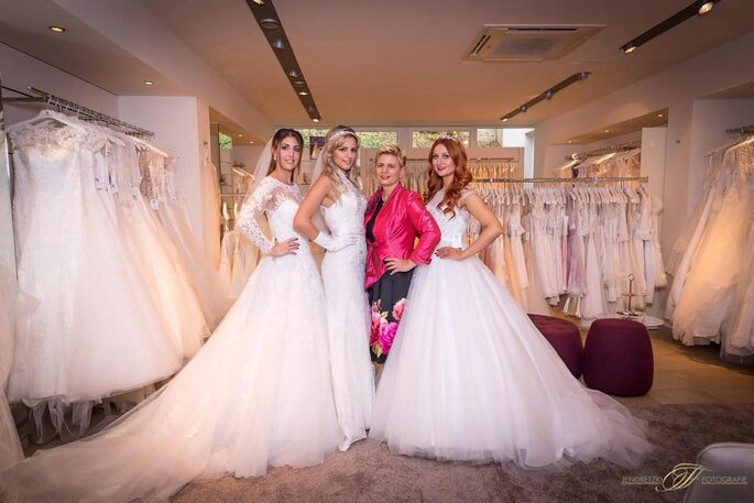 Drei Bräute und eine Frau mit pinker Lederjacke im Brautmodengeschäft Haus der Braut.