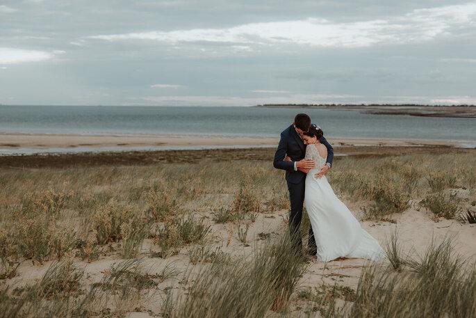 Des mariés s'enlacent face à l'océan.