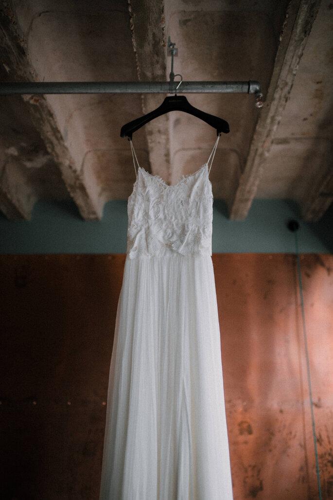 Das Brautkleid hängt an einem Holzbalken an der Decke.