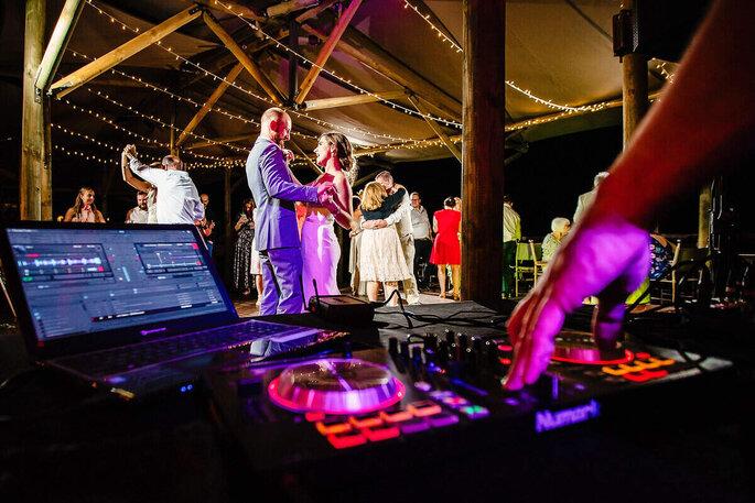 Deux mariés et leurs invités dansent sur les titres passés par un DJ de mariage
