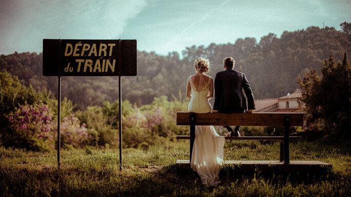Deux mariés assis de dos sur un banc au milieu d'un champ arboré et à côté d'un panneau départ du train