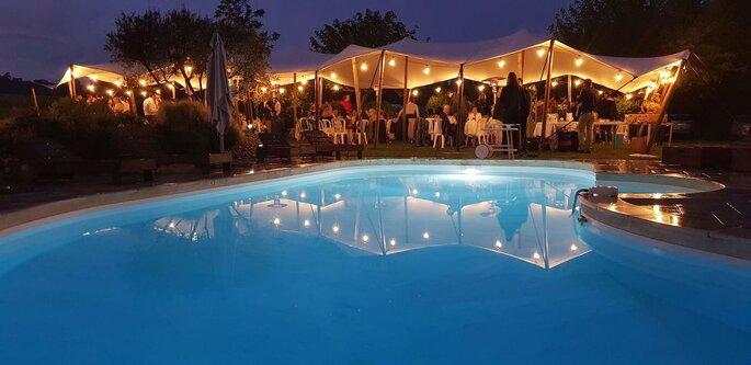Tentes illuminées sous lequel se déroule un dîner de mariage et piscine éclairée en premier plan