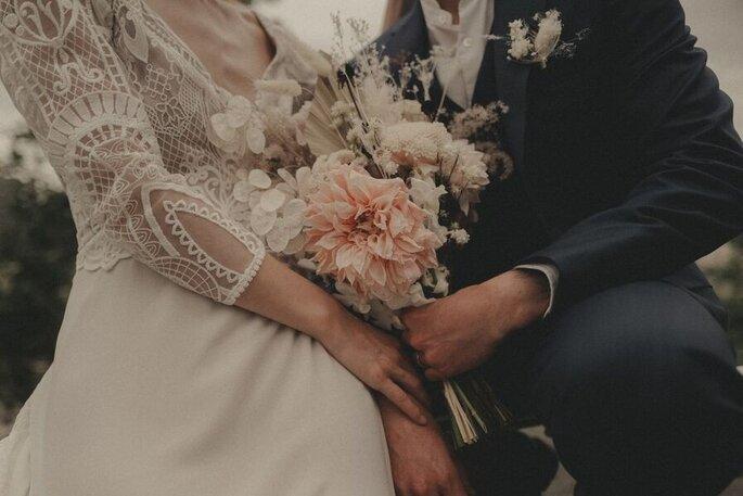 Un couple de mariés avec un bouquet de fleurs blanc et rose à la main