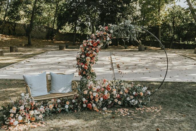 Arche fleurie en arc de cercle à côté d'un banc pour les mariés - idée mise en scène cérémonie laïque