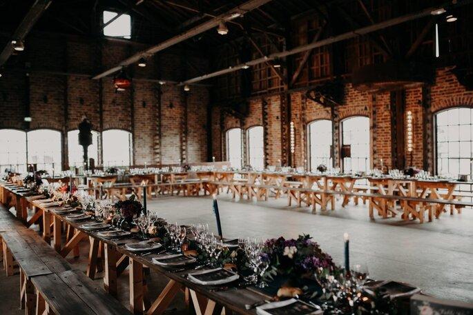 Une grande table est dressée pour un mariage dans une salle de réception rustique