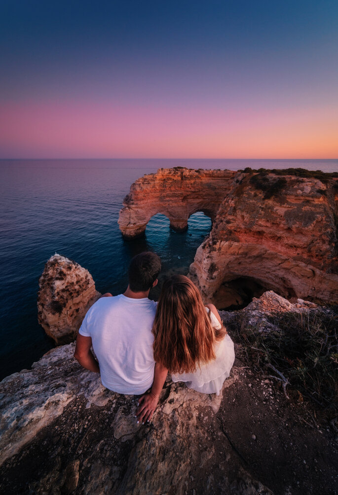 Paar schaut auf Sonnenuntergang über dem Meer