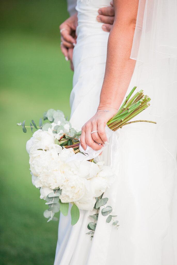 Une mariée enlacé par son mari, tenant son bouquet composé de fleurs blanches