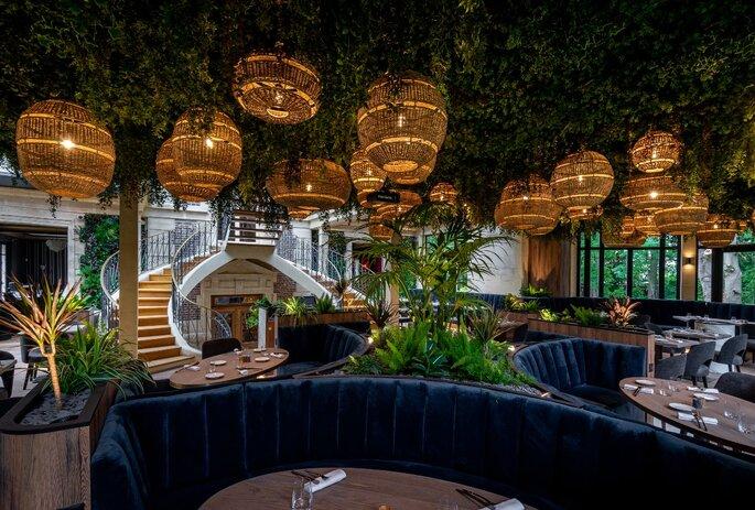 Salle de restaurant des Jardins d'Épicure, avec des lampions bohème, des plantes et un plafond végétalisme, des fauteuils en velours bleu nuit pour un dîner gastronomique de rêve