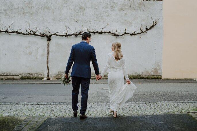 Brautpaar Händchen haltend von hinten