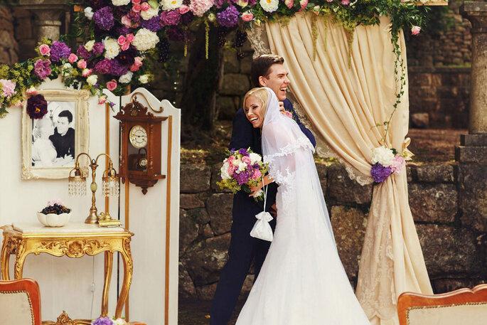 Ein Brautpaar hält sich in den Armen, Vintage-Dekoration im Hintergrund.
