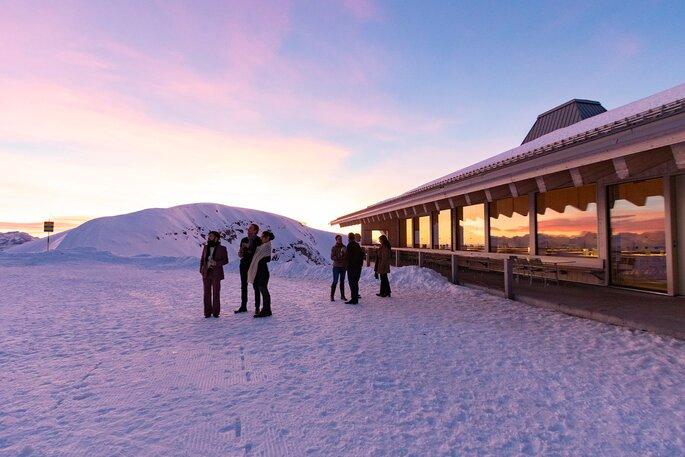 Drei Personen stehen beim Aperitif auf dem Chäserrugg vor dem Gipfelgebäude.