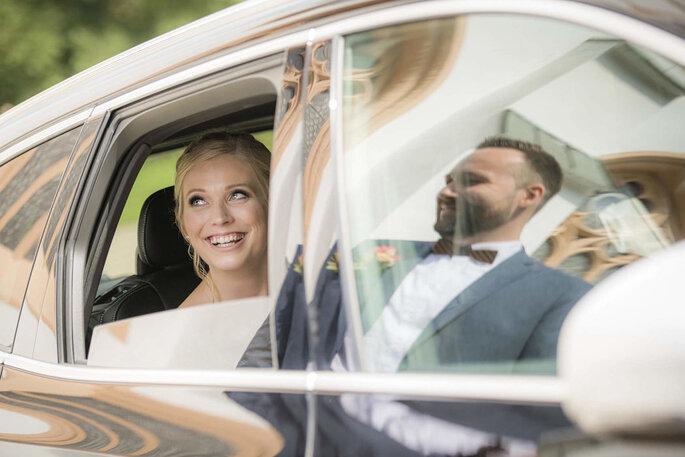 Eine Frau sitzt im Auto, der Bräutigam spiegelt sich in der Scheibe.
