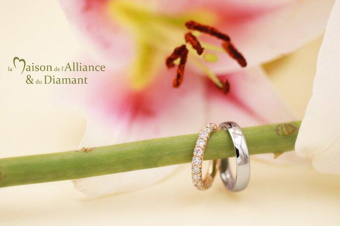 Deux alliances, l'une pour la future mariée en or, sertie de diamant et l'autre en or blanc pour le futur marié, disposées sur une branche de lys