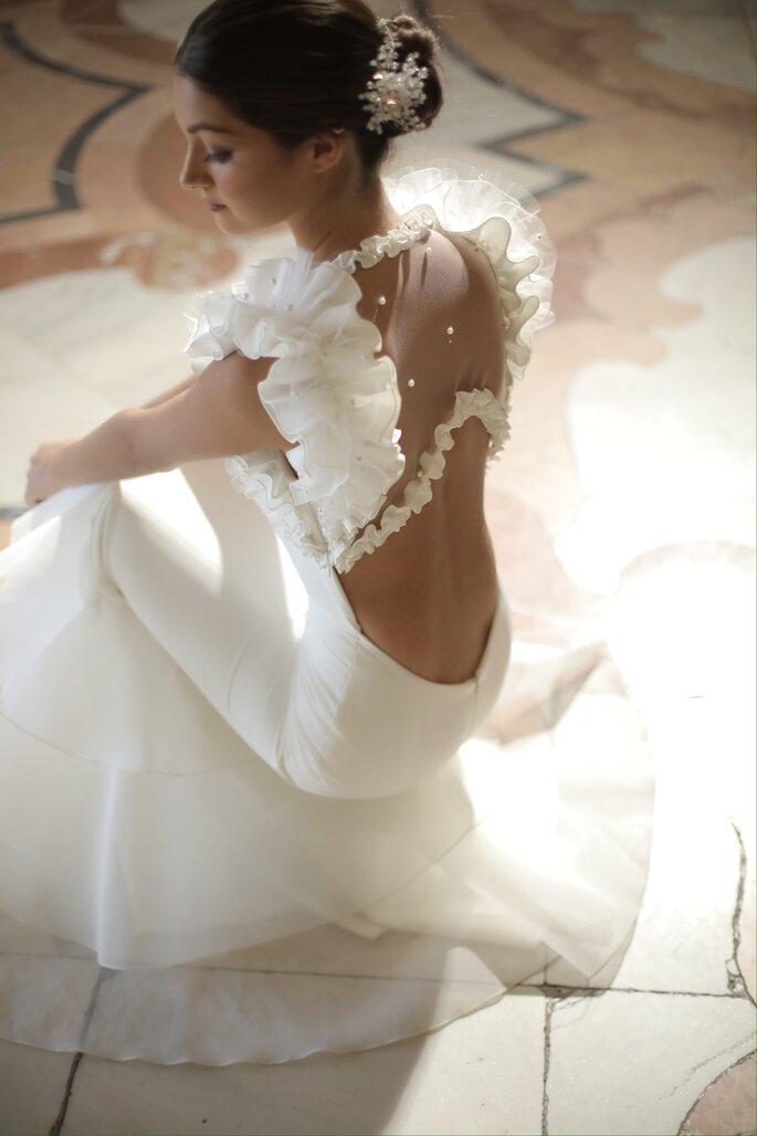 Vestido de novia con apertura en la espalda baja y mangas cortas de olanes y detalles de pedrería