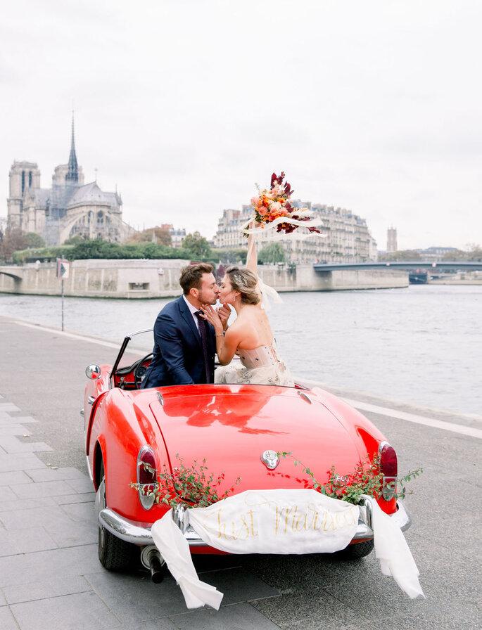 pareja feliz conduciendo coche rojo decorado para la boda