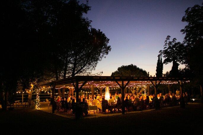 Un dîner de réception tenu sous une pergola, un soir d'été.
