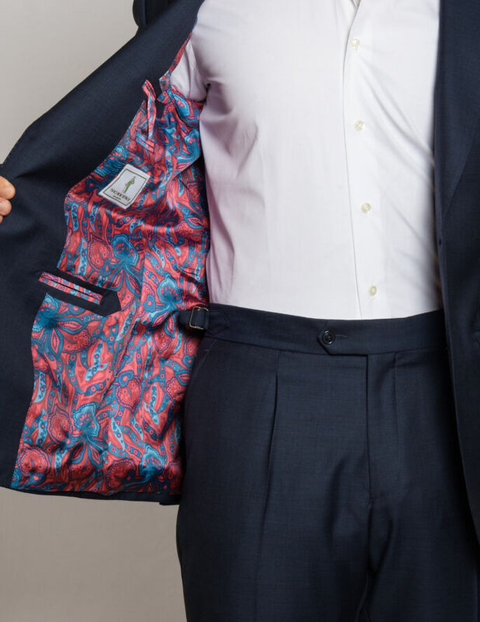 Un homme porte une chemise blanche et un costume de marié noire. À l'intérieur, la doublure de la veste est rouge avec des motifs bleus.
