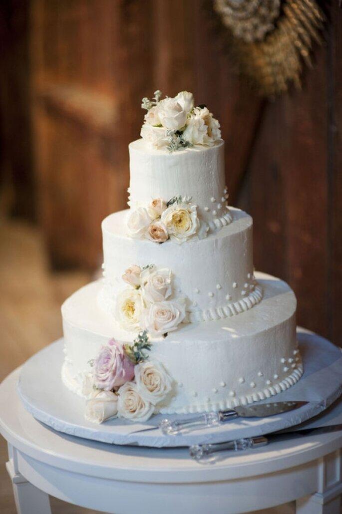 Pastel de boda blanco, con decoración floral en tonos blancos y lilas
