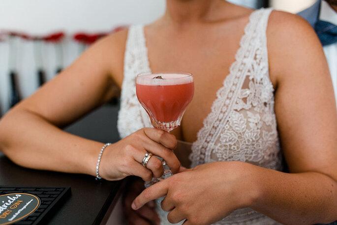 Die Braut hält einen tiefroten Cocktail in der Hand.