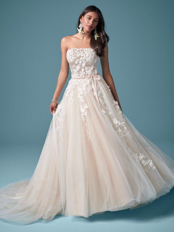Maggie Sottero vestido de novia en corte princesa strapless con escote recto, espalda de ilusión, de encaje sobre tul y una cinta con moño de adorno en la cintura.