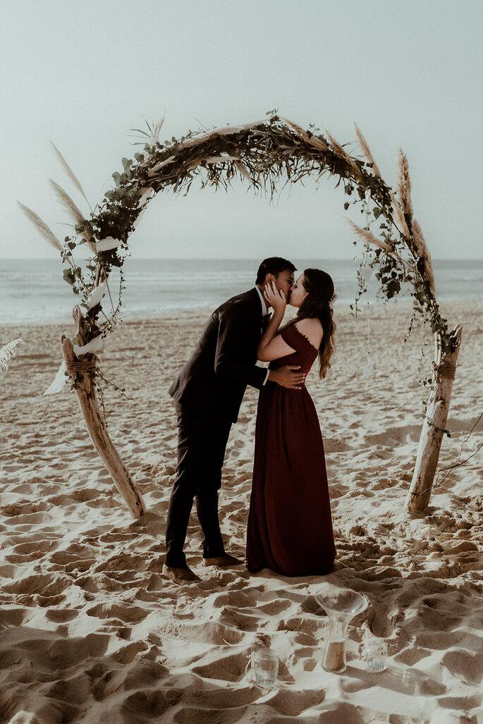Baiser couple arche mariage plage