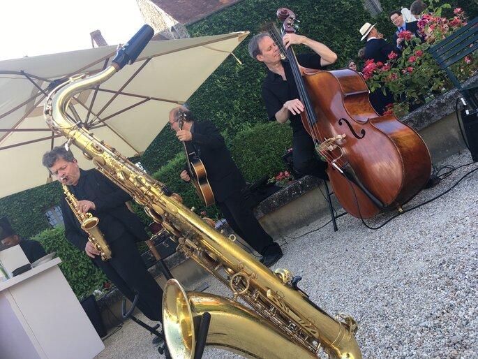 un saxophoniste, un bassiste et un guitariste jouant un morceau de musique du groupe Misterlive prod