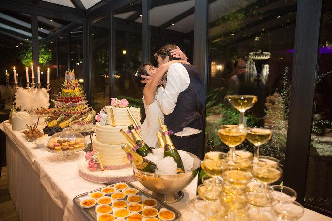 Les mariant s'embrassant devant le beau buffet de leur mariage