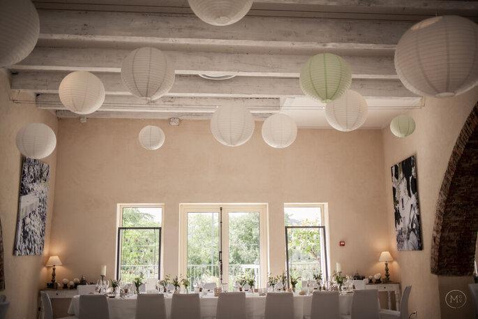 Une salle de réception lumineuse aux poutres apparentes. décorée de lampions de papier.