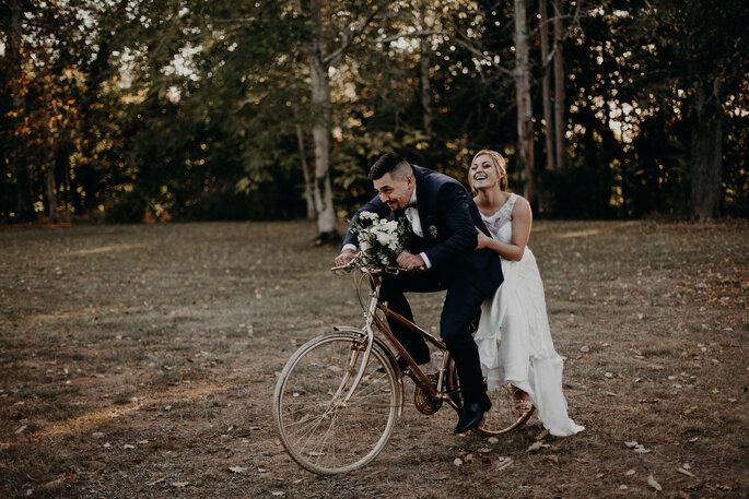 Un couple de mariée sur un vélo, en plein fou rire. Le marié tient un bouquet de fleurs à la main.