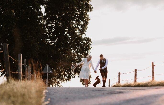 Brautpaar in Tracht in bayerischer Landschaft mit Dackel