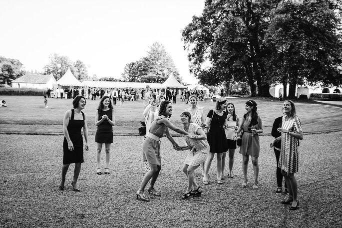Les invitées tendent d'attraper le bouquet de la mariée au vol dans le parc du château