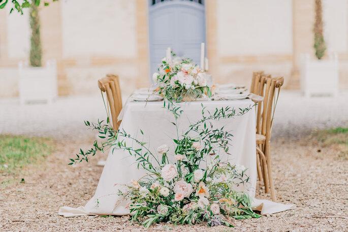 Une table de mariage dressée en extérieur ornée d'une décoration florale douce