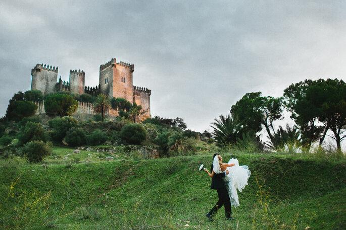 Bräutigam trägt Frau auf dem Arm. Im Hintegrund ist eine alte Burg zu sehen.
