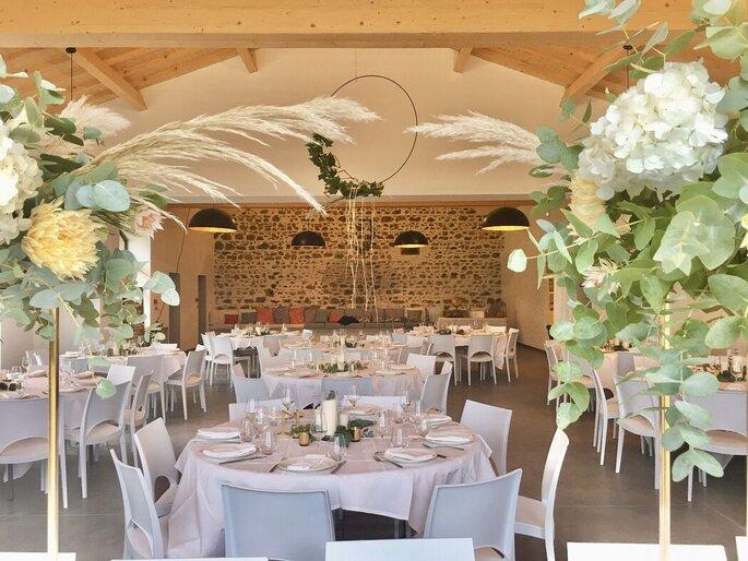 Salle de réception pour un mariage avec des murs de pierres et des poutres apparentes