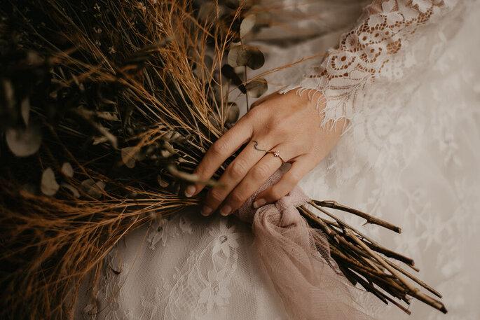 Une mariée tient dans sa main un bouquet de fleurs séchées.